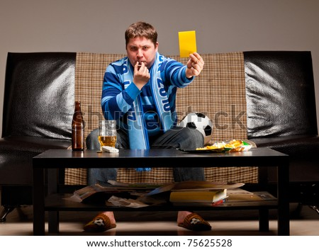 soccer fan is sitting on sofa with beer and showing yellow card at home - stock photo
