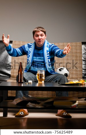 soccer fan is sitting on sofa with beer at home and applauding