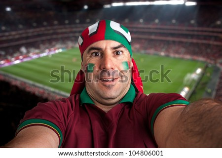 soccer fan stadium on the back with a portuguese scarf - stock photo