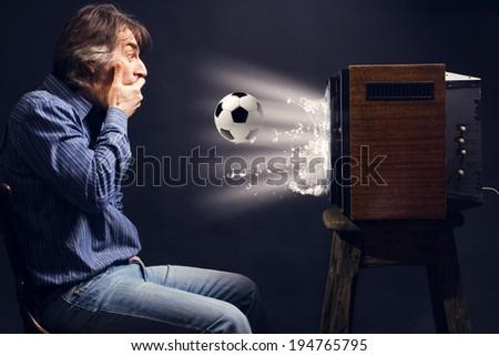 Soccer fan watching football on retro TV. - stock photo
