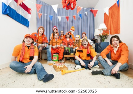Soccer fans sitting in a living room to watch a game of their national team - stock photo