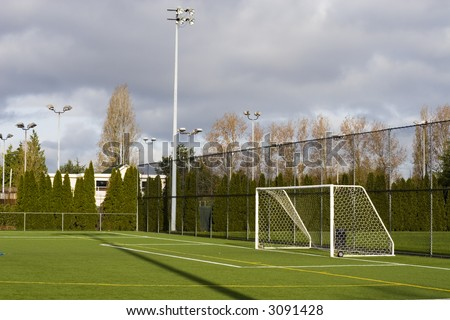 Soccer field with goal posts and light poles. - stock photo