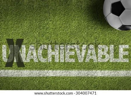 Soccer field with the text: Unachievable - stock photo