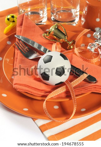 Soccer football celebration party table setting with pates, cutlery, glasses, trophy, soccer ball and decorations in orange and white team colors. - stock photo