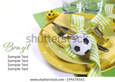 Soccer football celebration party table setting with pates, cutlery, glasses, trophy, soccer ball and decorations in yellow and green team colors with copy space. - stock photo