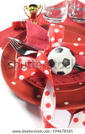 Soccer football celebration party table setting with pates, cutlery, glasses, trophy, soccer ball and decorations in red and white team colors - vertical, close up. - stock photo