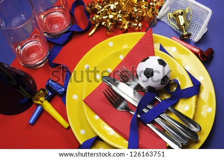 Soccer football celebration party table settings in red, yellow and blue team colors. - stock photo