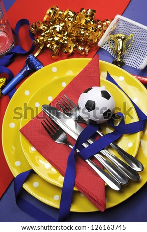 Soccer football celebration party table settings in red, yellow and blue team colors. Vertical portrait orientation. - stock photo