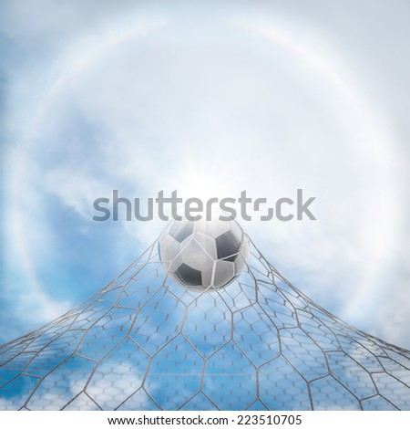 Soccer football in goal net with corona ring - stock photo