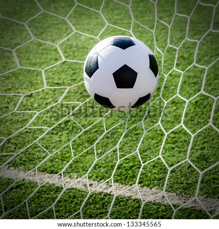 Soccer football in Goal net with green grass field. - stock photo