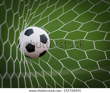 Soccer football in Goal net with green grass field