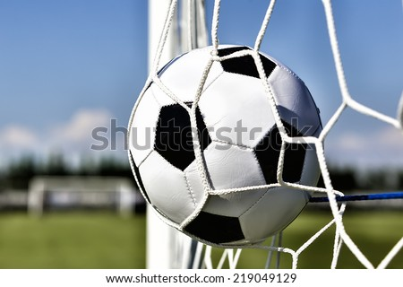 Soccer football in Goal net with sky field. Tonal contrast - stock photo