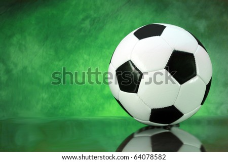 Soccer football on brilliant green background with copy space - stock photo