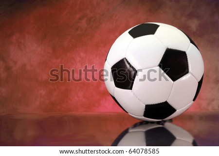 Soccer football on brilliant red background with copy space - stock photo