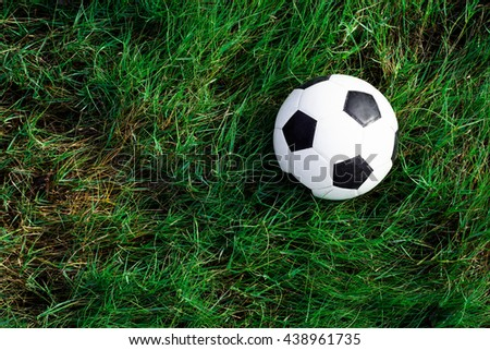 Soccer football on grass field, Soccer ball in fresh green summer or spring field grass - stock photo