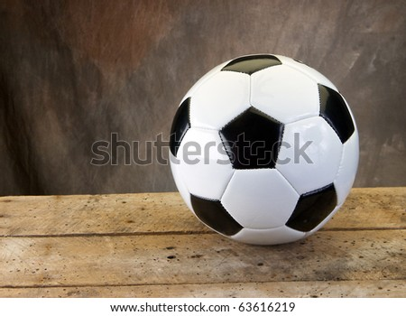 Soccer football on old vintage wood table with tan background and copy space - stock photo