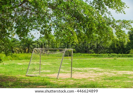 soccer goal on playground sand in front of rubber trees.