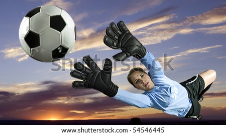 Soccer goalie blocks ball against sunset backdrop. Horizontal shot. - stock photo