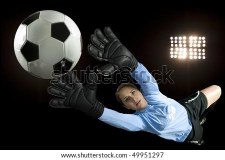 soccer goalie blocks ball in stadium - stock photo