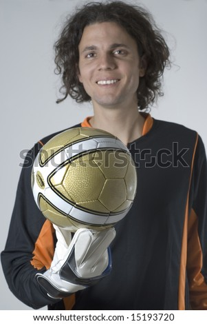 Soccer goalie wearing a jersey and gloves smiles as he holds a soccer ball. Vertically framed photograph - stock photo