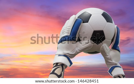 Soccer goalkeeper's hands reaching for the ball with beautiful sky - stock photo
