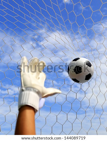 Soccer goalkeeper's hands reaching for the ball, with net and sky in the background - stock photo