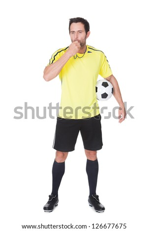 Soccer judge standing with ball. Isolated on white background