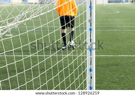 Soccer net with a goalkeeper with the ball in his feet