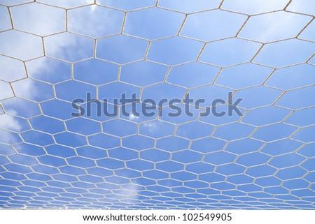 Soccer net with on blue sky background - stock photo