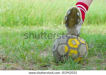 Soccer on old and bad field with shabby ball closeup. - stock photo