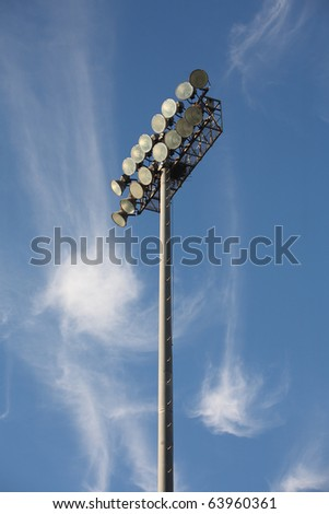 Soccer or Baseball Floodlights against a blue sky with strange cirrus cloud formations - stock photo