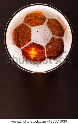 soccer or football ball symbol on foam of fresh lager beer glass on black table, view from above - stock photo