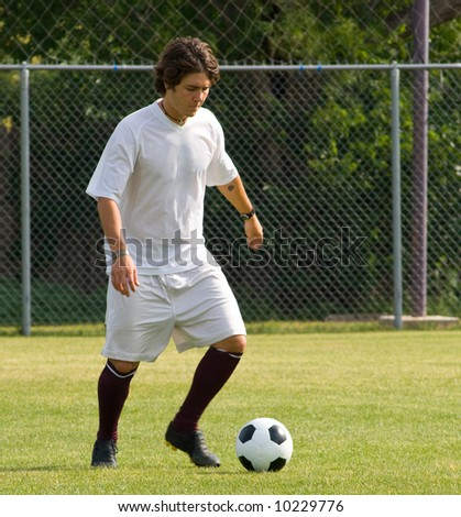 Soccer or football player in white dribbling soccer ball - stock photo