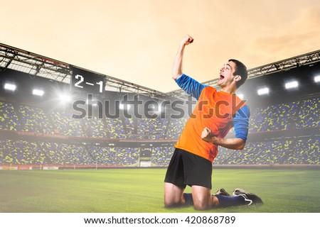 soccer or football player is celebrating goal on stadium - stock photo