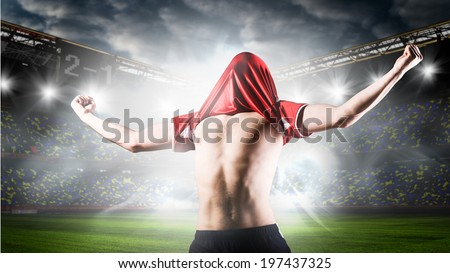 soccer or football player is celebrating goal on stadium with his jersey on head - stock photo