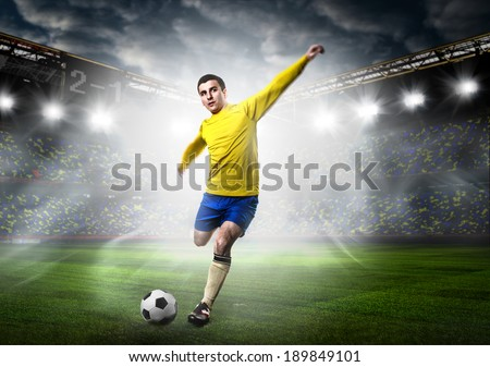 soccer or football player is kicking ball on stadium