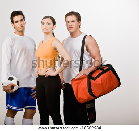 Soccer player and athletic friends in sportswear with soccer ball and gym bag - stock photo
