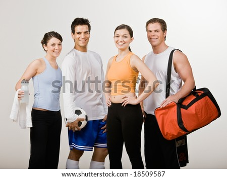 Soccer player and athletic friends in sportswear with soccer ball, gym bag and water bottle - stock photo