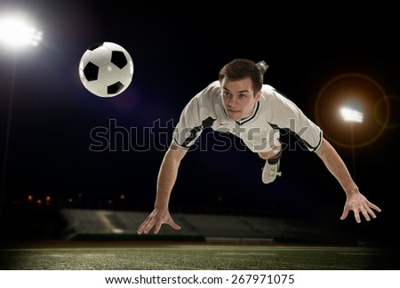 Soccer player diving in the air inside a stadium - stock photo
