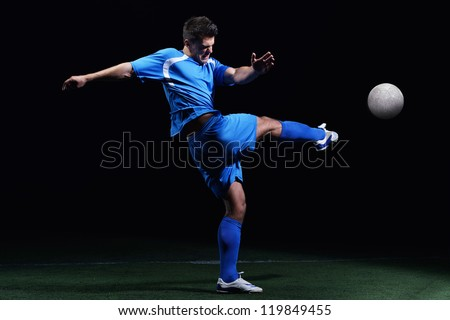 soccer player doing kick with ball on football stadium  field  isolated on black background - stock photo