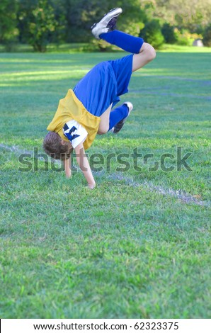 Soccer player falling on sideline into hand stand - stock photo