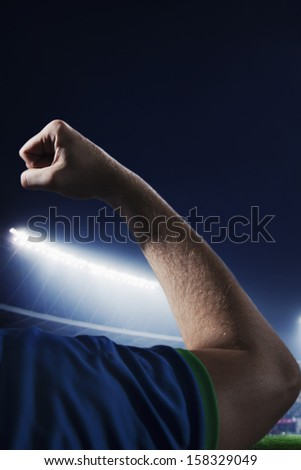 Soccer player flexing bicep in stadium at night