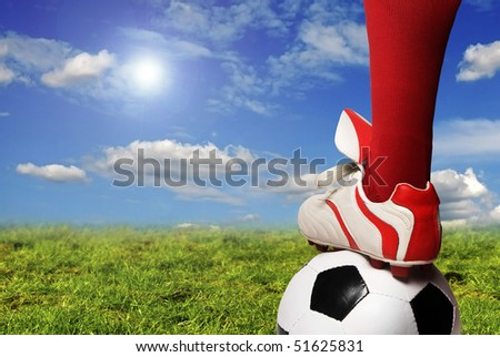 soccer player foot and ball in the pitch - stock photo