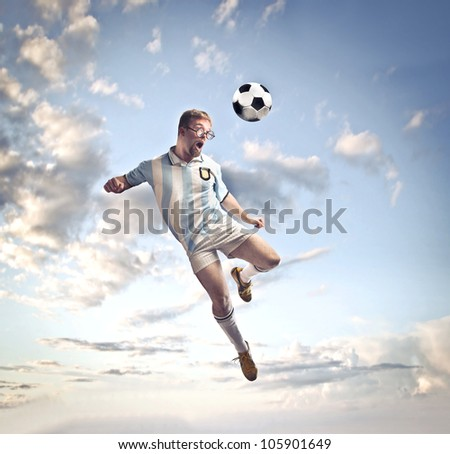 Soccer player head-shooting a football in the sky - stock photo