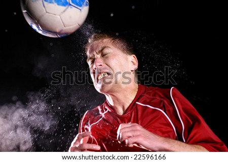 Soccer player hitting ball with head - stock photo