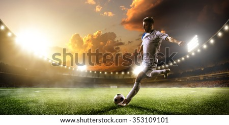 Soccer player in action on sunset stadium background - stock photo