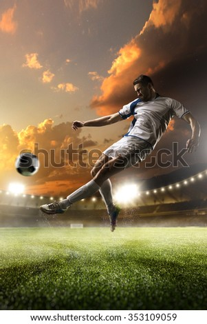 Soccer player in action on sunset stadium with background - stock photo