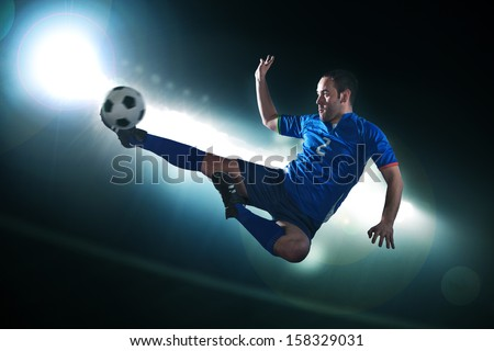 Soccer player in mid air kicking the soccer ball - stock photo
