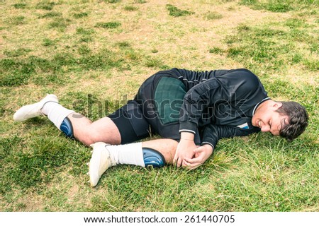 Soccer player injured during amateur football match - Concept of sport failure and physical accident - stock photo