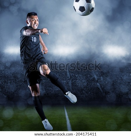 Soccer player kicking ball in a large stadium - stock photo